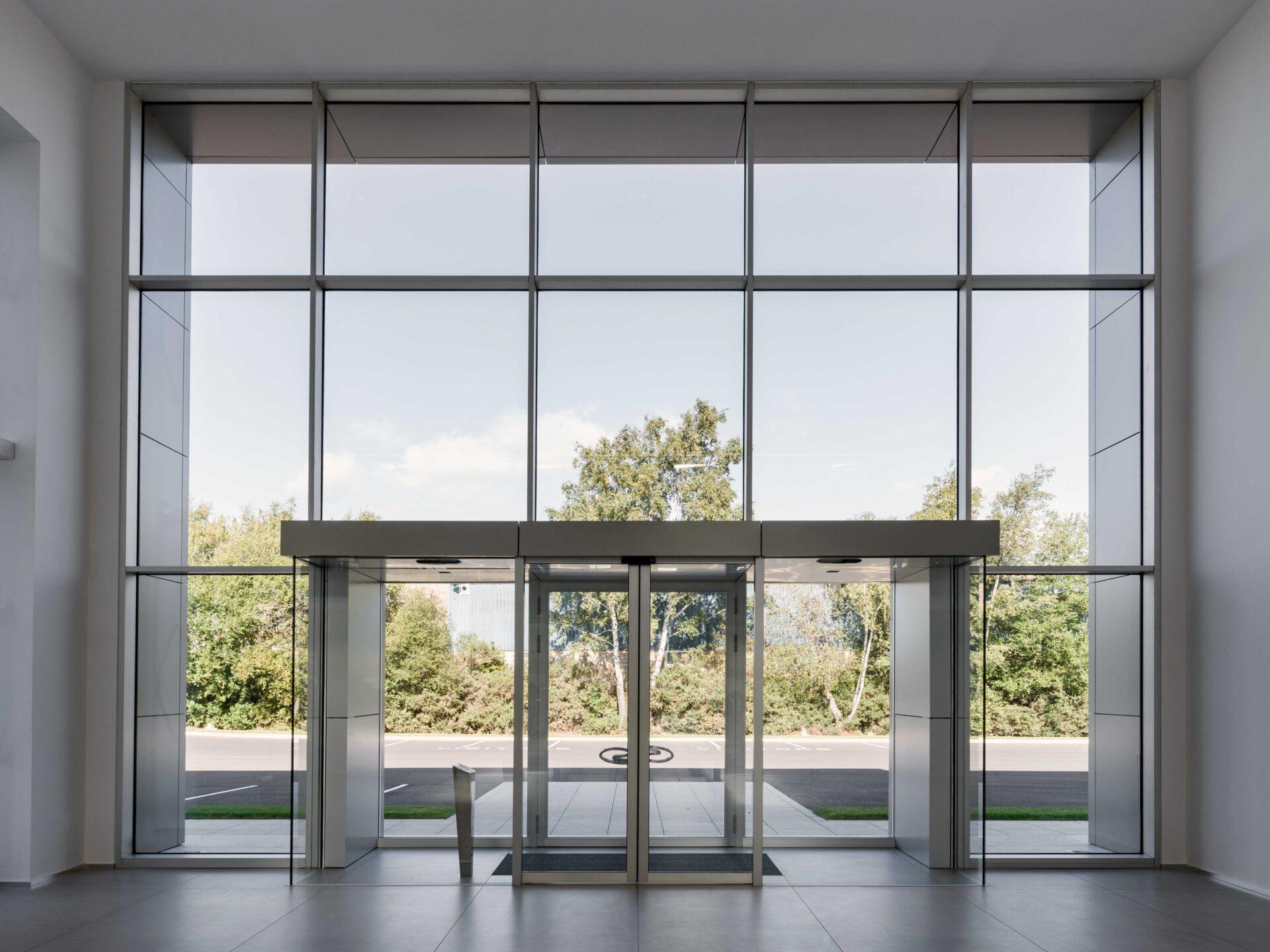 Nella hall di ingresso del polo industriale Superior, Thema ha realizzato la doppia bussola in cui il peso della facciata principale dell'edificio è scaricato sul traverso che funge da portale.