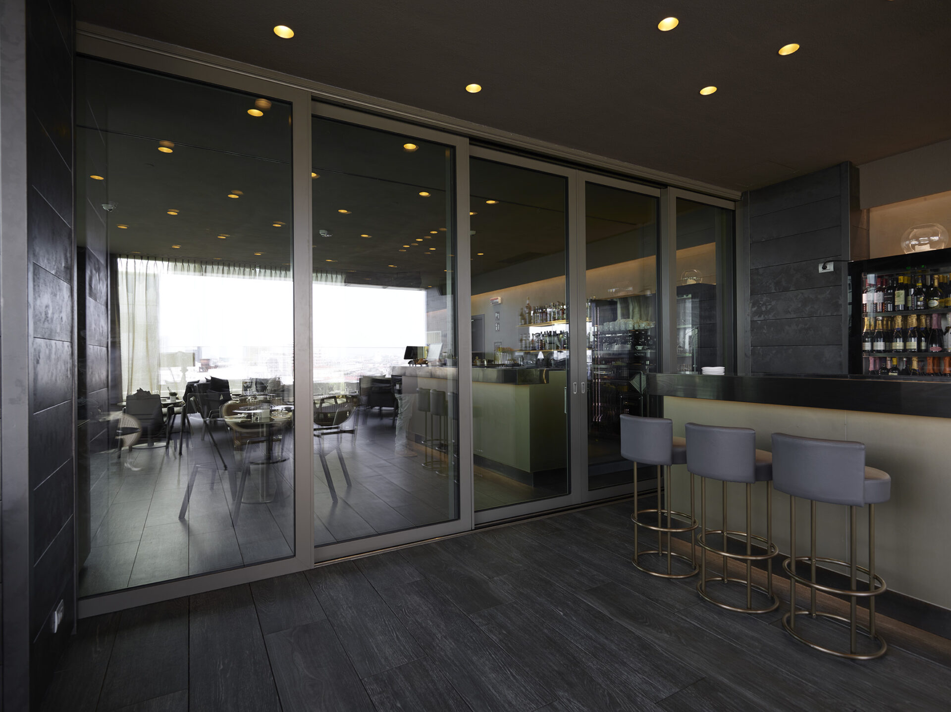 Thema per l'ultimo piano dell'hotel, nella zona ristorante, ha realizzato i parapetti e i serramenti scorrevoli completamente apribili che si affacciano sia sull'esterno sia sull'interno della sala, per un effetto tutto vetro.